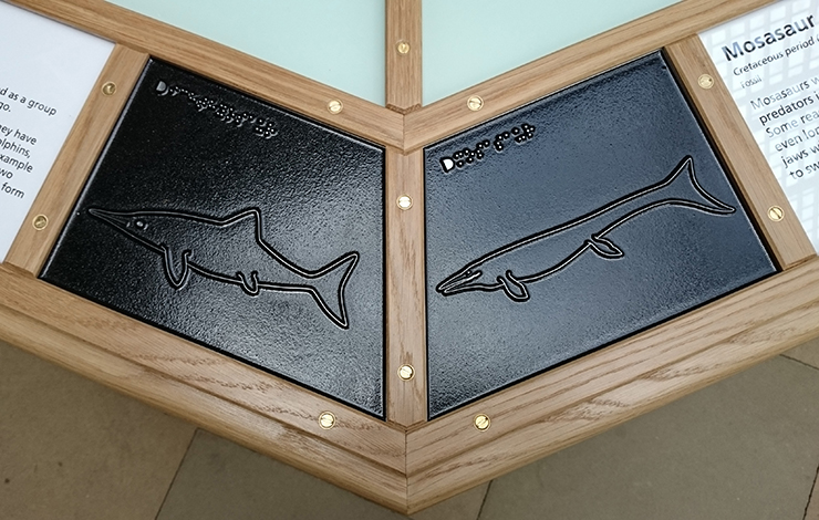 Metal tactile line drawings of an Ichthyosaur and a Mosasaur.