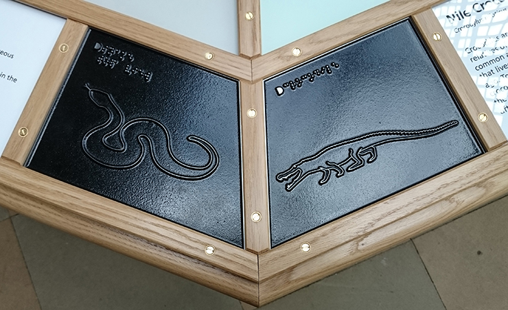 Metal tactile line drawings of a Snake and a Crocodile.