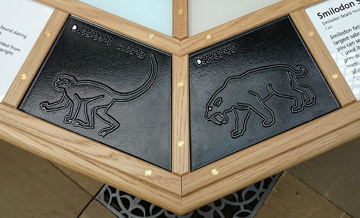 Metal tactile line drawings of a Squirrel Monkey and a Smilodon.